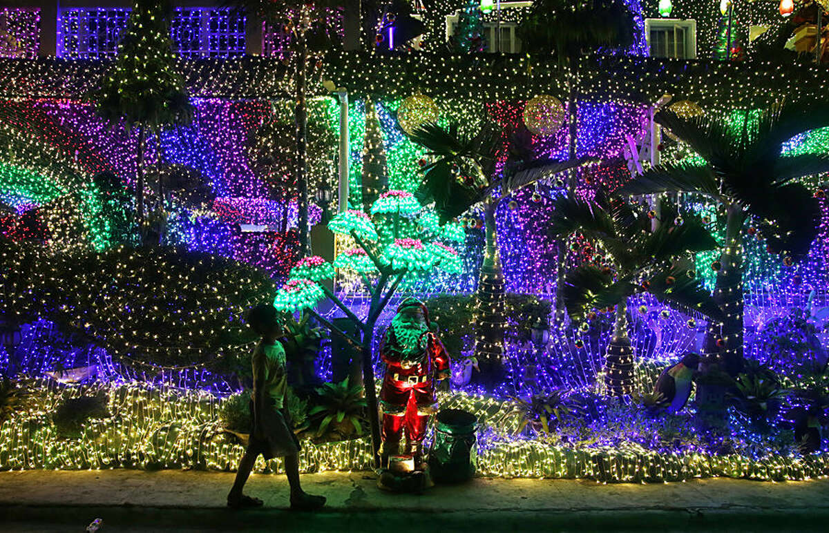 In this Sunday, Nov. 29, 2015 photo, a Filipino boy walks beside Christmas decorations outside a house in Cainta, Rizal province, east of Manila, Philippines. The house is drawing huge crowds, especially during weekends, with visitors using the bright lights and festive Christmas decors as their backdrop for selfies with families and friends. (AP Photo/Aaron Favila)