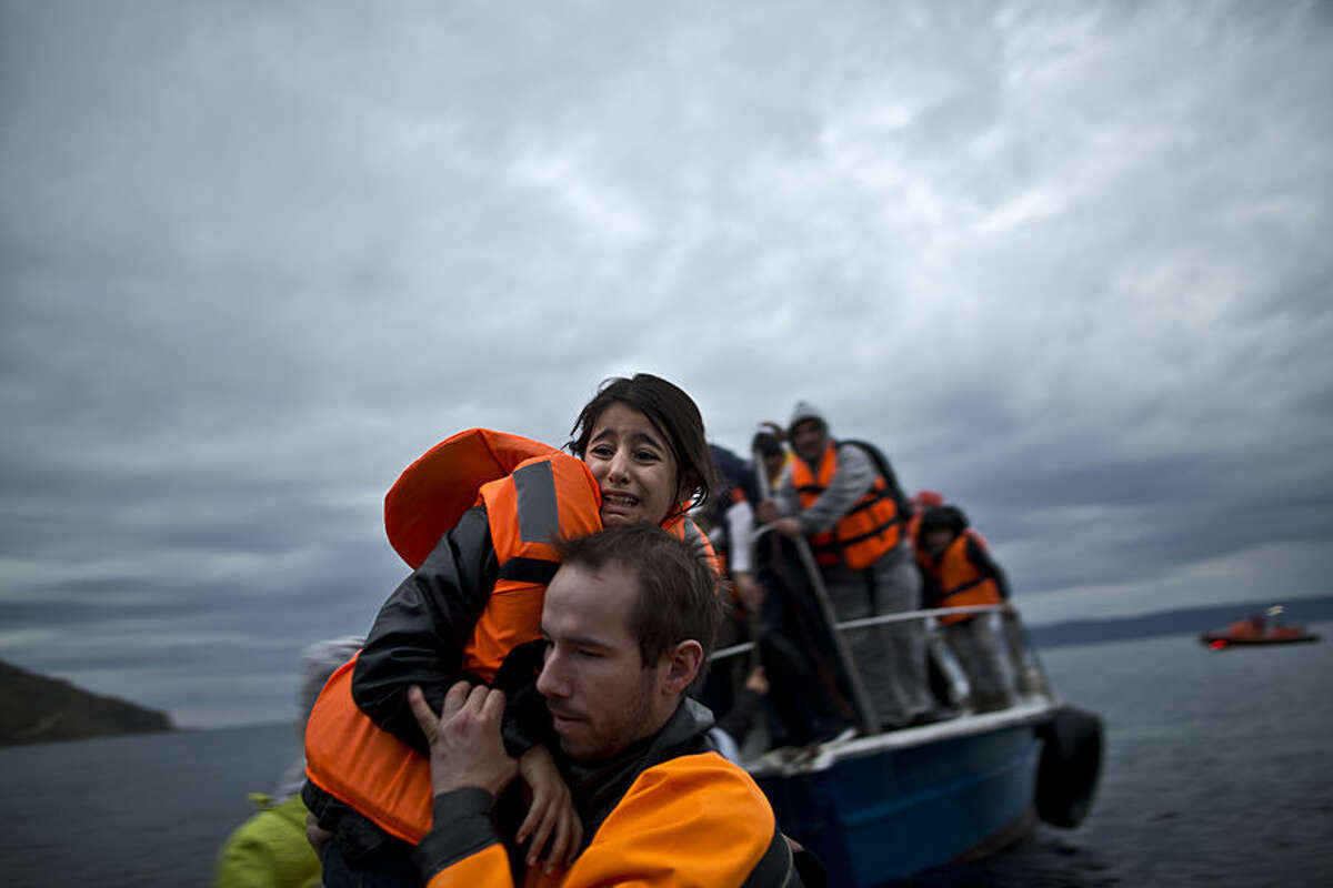 A young refugee girl is carried by a volunteer off a vessel to the shore shortly after arriving with her family from the Turkish coast to the northeastern Greek island of Lesbos, Thursday, Dec. 3, 2015. The European Union's police agency says 23 suspects have been arrested in raids targeting an organized crime gang that smuggled thousands of migrants into Europe. Greece has been the main point of entry into the EU for about 700,000 migrants and refugees so far this year. (AP Photo/Muhammed Muheisen)