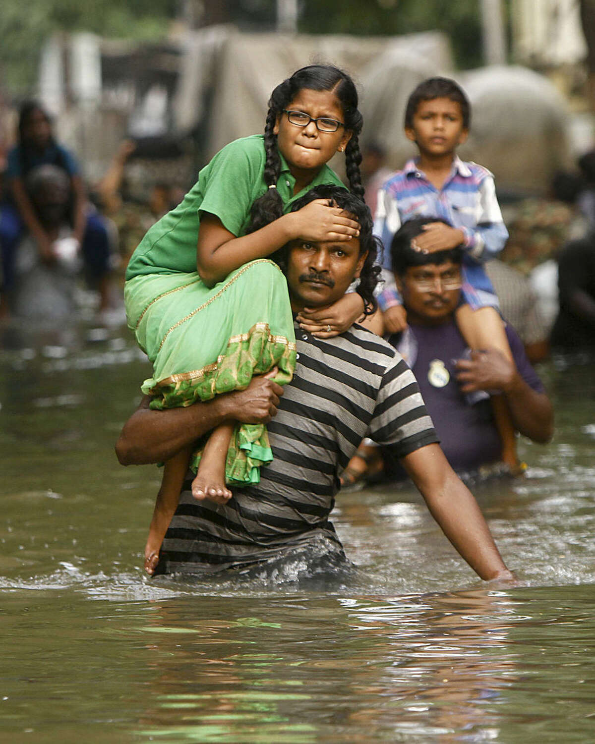 People carry children on their shoulders and wade through flood waters in Chennai, India, Thursday, Dec. 3, 2015. The heaviest rainfall in more than 100 years has devastated swathes of the southern Indian state of Tamil Nadu, with thousands forced to leave their submerged homes and schools, offices and a regional airport shut for a second day Thursday.( AP Photo)