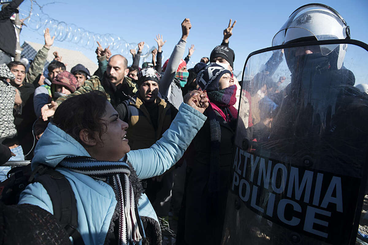 Stranded migrants shout slogans in front of Greek policemen at the Greek-Macedonian border, near the northern Greek village of Idomeni, Thursday, Dec. 3, 2015. Macedonian authorities are allowing only people from the war-wracked countries of Syria, Afghanistan and Iraq to cross from Greece on their way to other European Union countries, leading to protests from those from other countries who have been blocking the crossing for all since Wednesday. (AP Photo/Giannis Papanikos)