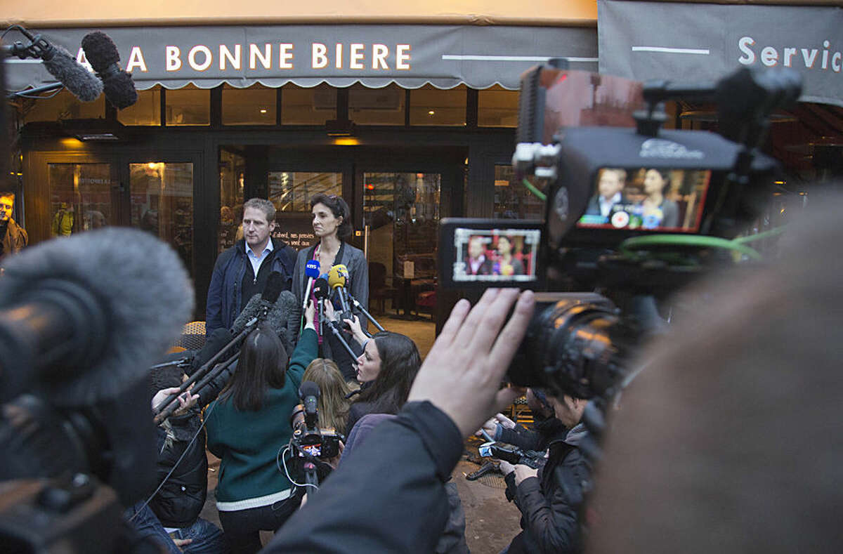 Audrey Bily, right, and Romain Debray, managers of La Bonne Biere, speak to the media in front of their cafe in Paris during its reopening Friday, Dec. 4, 2015. The cafe where five people were killed by a squad of Islamic extremist gunmen on Nov. 13, terrorizing central Paris reopened for business Friday. (AP Photo/Jacques Brinon)