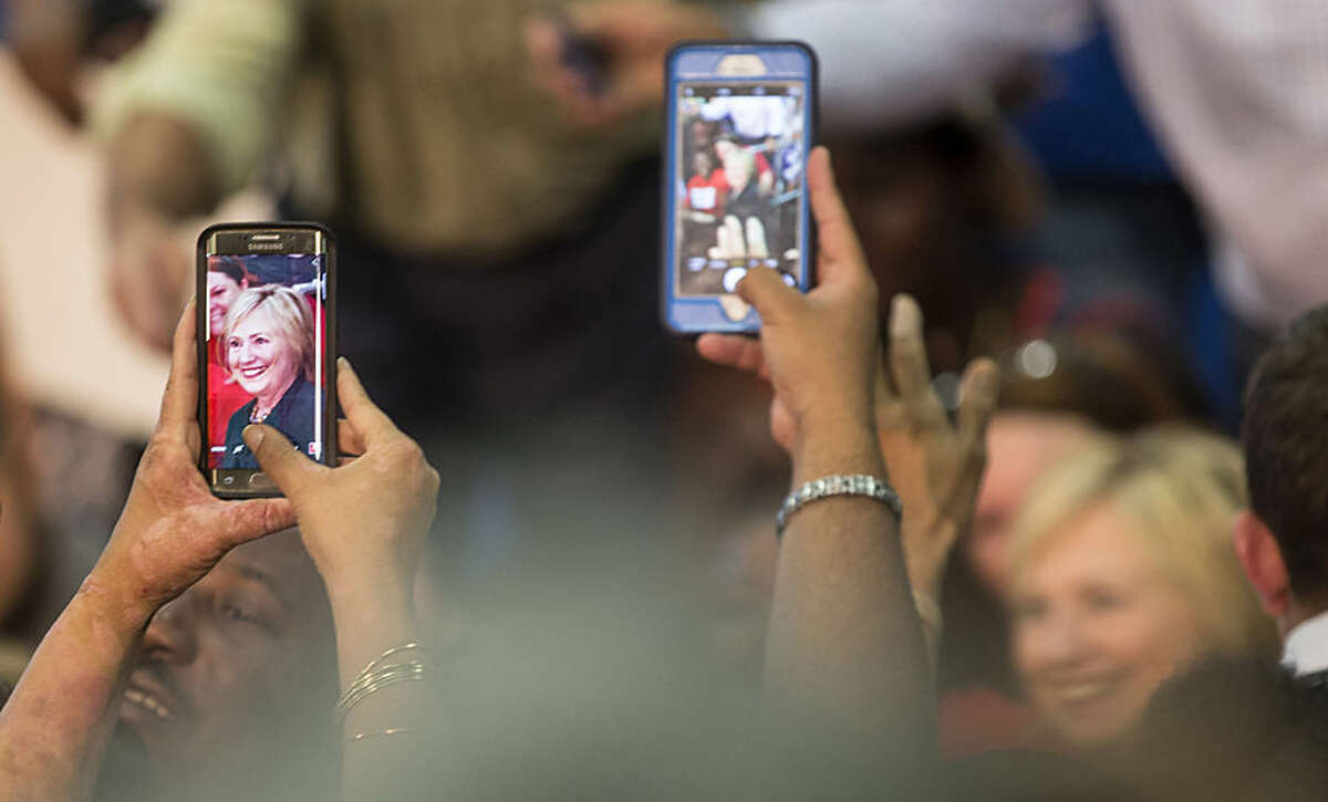 Guests use their cellphones to captures the likeness of Democratic presidential candidate Hillary Clinton at a Grassroots Organizing Event at the Meadow Woods Recreation Center, Wednesday, Dec., 2, 2015, in Orlando, Fla. (AP Photo/Willie J. Allen Jr.)