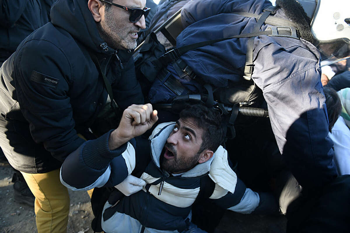Greek policemen scuffle with stranded migrants, who try to block the crossing for refugees at the Greek-Macedonian border, near the northern Greek village of Idomeni, Thursday, Dec. 3, 2015. Macedonian authorities are allowing only people from the war-wracked countries of Syria, Afghanistan and Iraq to cross from Greece on their way to other European Union countries, leading to protests from those from other countries who have been blocking the crossing for all since Wednesday. (AP Photo/Giannis Papanikos)
