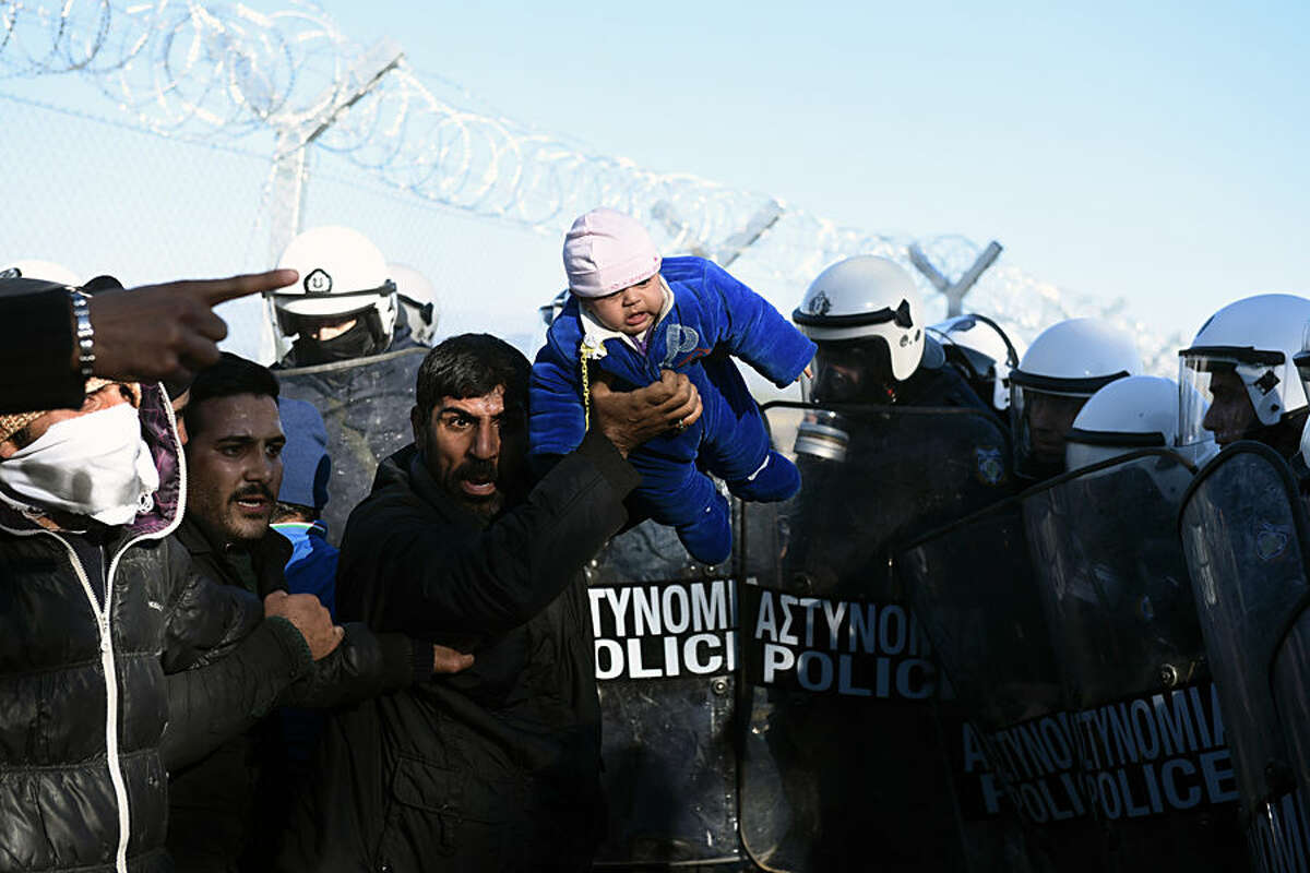 A stranded migrant holds up a baby as Greek policemen guard the Greek-Macedonian border, near the northern Greek village of Idomeni, Thursday, Dec. 3, 2015. Macedonian authorities are allowing only people from the war-wracked countries of Syria, Afghanistan and Iraq to cross from Greece on their way to other European Union countries, leading to protests from those from other countries who have been blocking the crossing for all since Wednesday. (AP Photo/Giannis Papanikos)
