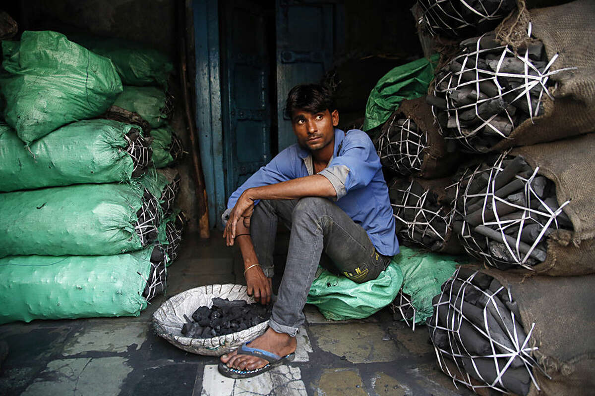 A worker at a retail coal store awaits customers in Mumbai, India, Thursday, Dec.3, 2015. An Indian delegate at U.N. climate talks says India will be able cut back on its carbon emissions if money is made available to boost renewable energy in an envisioned climate agreement in Paris.India's negotiators want to make sure that any deal in Paris doesn't restrict India's ability to expand its economy and electricity access to about 300 million people who currently have none. That means it's hard for India to abandon coal power, a key source of carbon emissions that currently accounts for about 60 percent of its power capacity.(AP Photo/Rajanish Kakade)