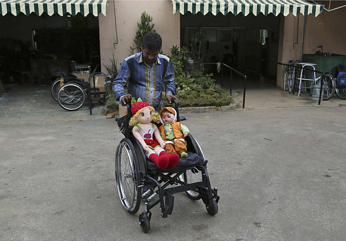 A staff member pushes a wheelchair carrying stuffed toys at the Association of People with Disability run school in Bangalore, India, Thursday, Dec. 3, 2015. According to the United Nations, an estimated one billion people, or approximately 15 per cent of the world's population, live with some form of disability. (AP Photo/Aijaz Rahi)