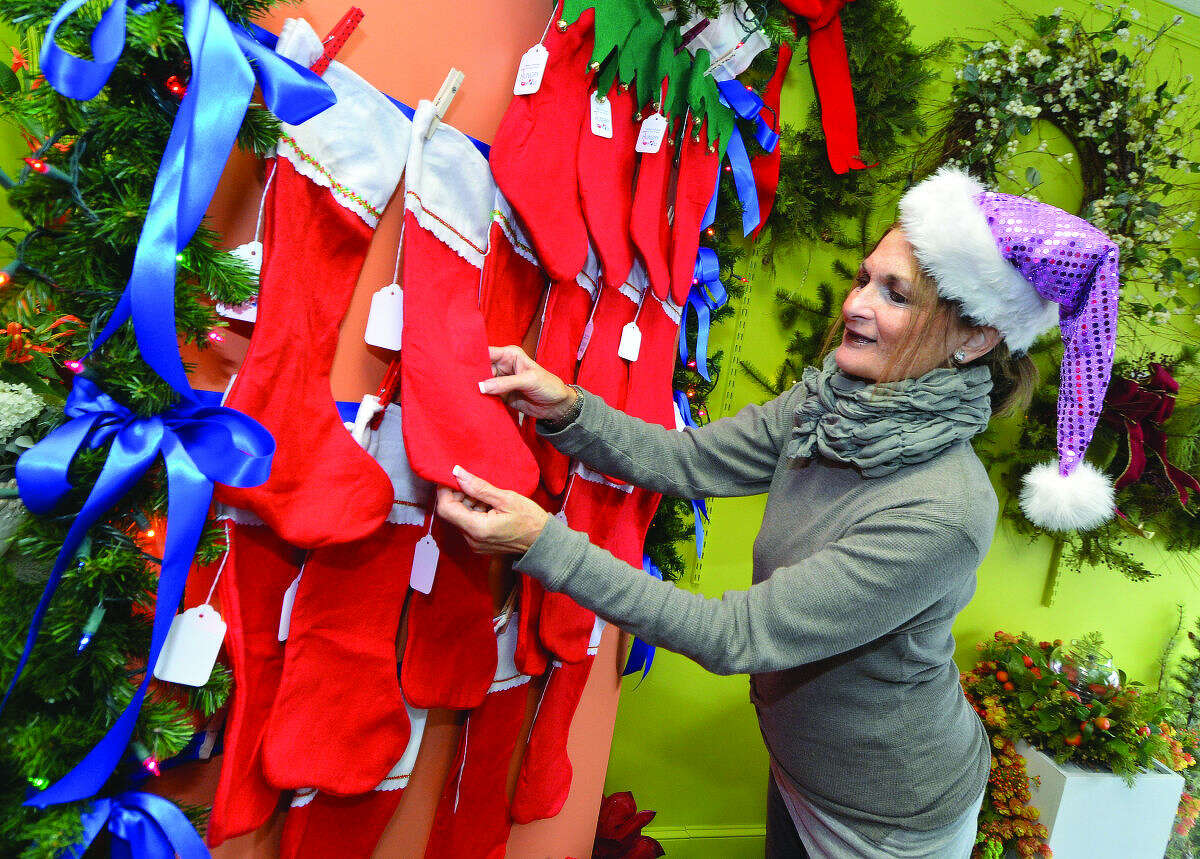 Hour Photo/Alex von Kleydorff Danna DiElsi , owner of The Silk Touch in Norwalk arranges some of the Stockings for people to pick up and fill for children less fortunate this holiday