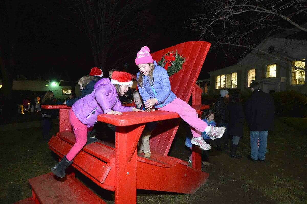 Hour Photo/Alex von Kleydorff 7yrn old Jenna Mancuso and 7yr old Ellery Worst climb onto the big red chair during the Wilton tree lighting and Holiday Stroll on friday night