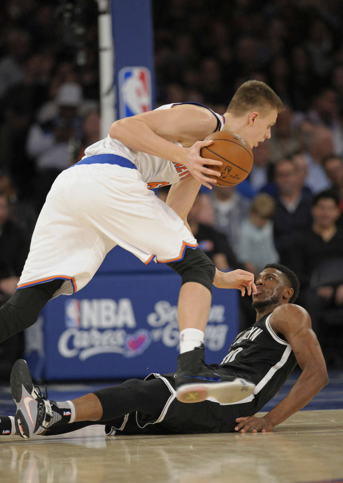 New York Knicks' forward Kristaps Porzingis, left, runs over Brooklyn Nets forward Thaddeus Young during the second quarter of an NBA basketball game Friday, Dec. 4, 2015, at Madison Square Garden in New York. (AP Photo/Bill Kostroun)