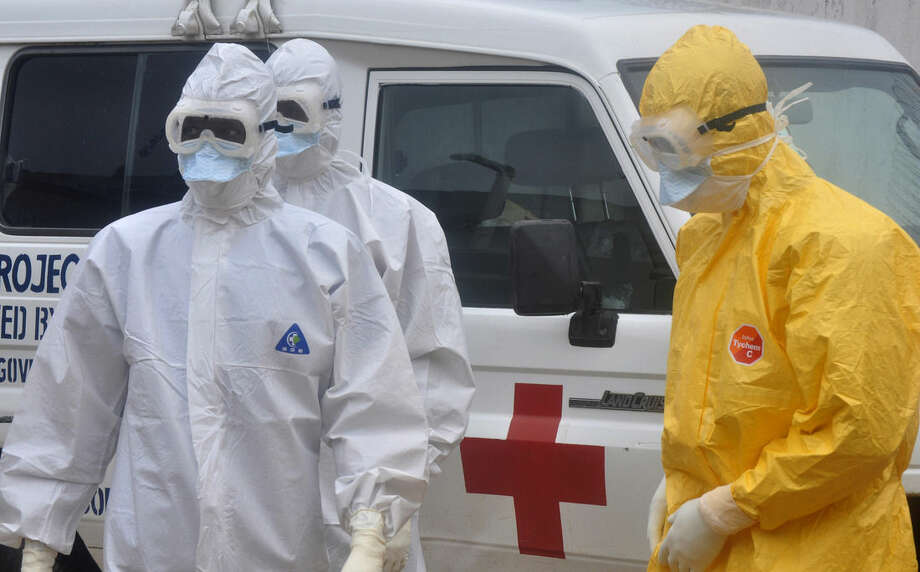 Health workers in protective gear wait to carry a body of a person suspected to have died from Ebola not in frame Monrovia ,Liberia. Monday, Oct. 13, 2014. Some nurses in Liberia defied calls for a strike on Monday and turned up for work at hospitals amid the worst Ebola outbreak in history. In view of the danger of their work, members of the National Health Workers Association are demanding higher monthly hazard pay. The association has more than 10,000 members, though the health ministry says only about 1,000 of those are employed at sites receiving Ebola patients. (AP Photo/ Abbas Dulleh)