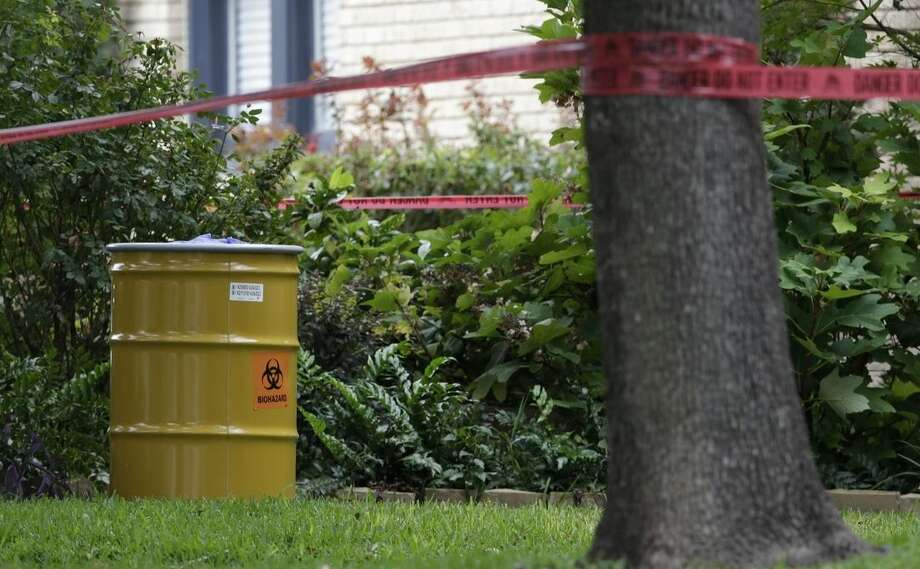 A hazmat container sits outside the apartment building of a hospital worker, Sunday, Oct. 12, 2014, in Dallas. The Texas health care worker, who was in full protective gear when they provided hospital care for Ebola patient Thomas Eric Duncan, who later died, has tested positive for the virus and is in stable condition, health officials said Sunday. (AP Photo/LM Otero)