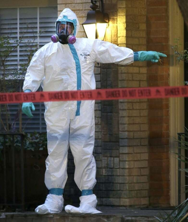 A hazmat worker points to the entrance of an apartment building of a hospital worker, Sunday, Oct. 12, 2014, in Dallas. The Texas health care worker, who was in full protective gear when they provided hospital care for Ebola patient Thomas Eric Duncan, who later died, has tested positive for the virus and is in stable condition, health officials said Sunday. (AP Photo/LM Otero)