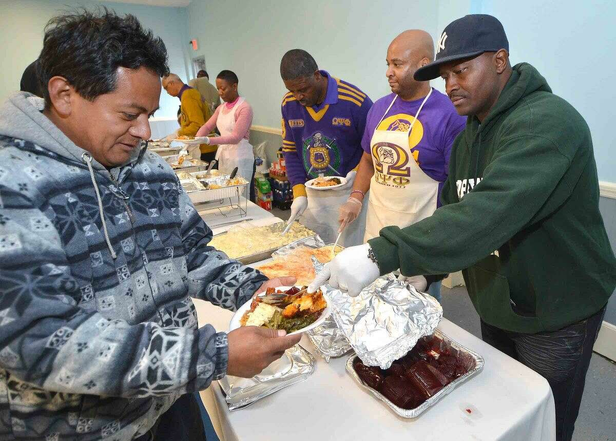 Hour Photo/Alex von Kleydorff Travis Simms and members of the Fraternity Omega Psi Phi gets the cranberry sause on the plates during the Community Thanksgiving Dinner sponsored by Ernie and Martha Dumas and South Norwalk residents