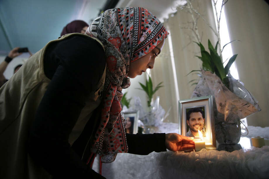 Khadija Zadeh lights candles set up next to the framed photos of 14 victims killed in in Wednesday's shooting rampage before the start of the memorial service at the Islamic Community Center of Redlands, Sunday, Dec. 6, 2015, in Loma Linda, Calif. The FBI said it is investigating the rampage as a terrorist attack. (AP Photo/Jae C. Hong)