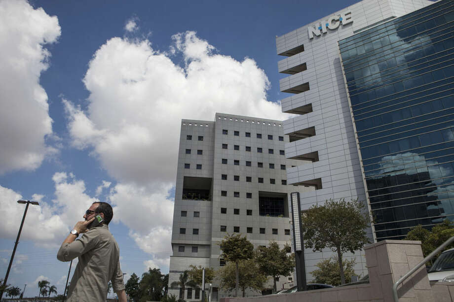 In this photo taken Sunday, Sept. 14, 2014 an Israeli man speaks on the phone next to the NICE Systems Ltd buildings in the city of Raanana, Israel. Businesses and governments around the world are increasingly turning to voice biometrics, or voiceprints, to replace passwords and fight fraud. Wells Fargo, the San Francisco-based bank, uses voices screening technology, also known as voice biometric blacklists, provided by NICE. (AP Photo/Dan Balilty)