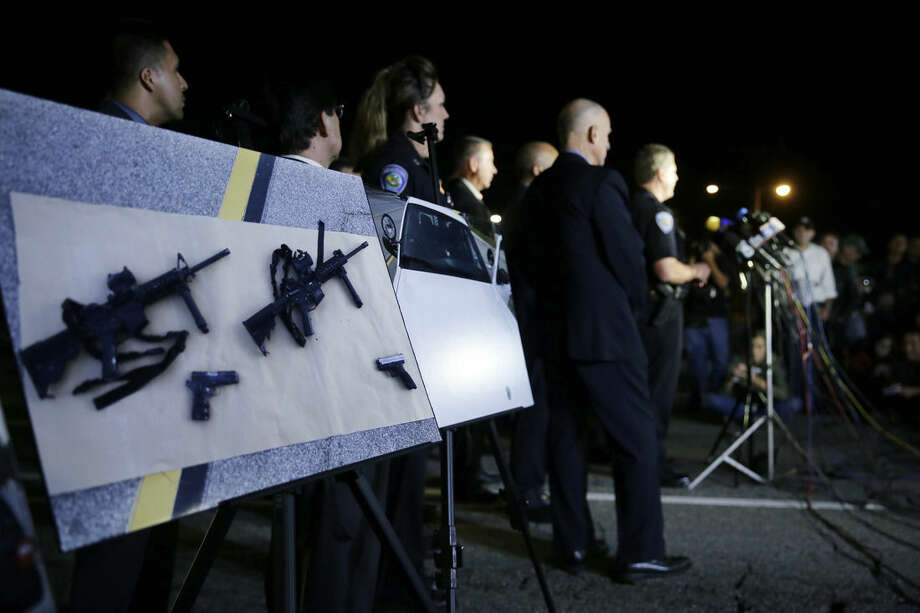 Police crime photos are displayed during a press conference near the site of yesterday's mass shooting on Thursday, Dec. 3, 2015 in San Bernardino, Calif. A husband and wife on Wednesday, dressed for battle and carrying assault rifles and handguns, opened fire on a holiday banquet for his co-workers, killing at least 14 people and seriously wounding more than a dozen others in a precision assault, authorities said. Hours later, the couple died in a shootout with police. (AP Photo/Chris Carlson)