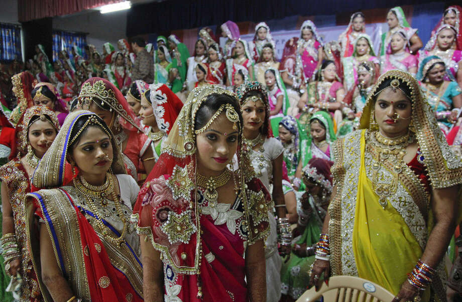 Indian brides leave after a group photo before a mass wedding hosted by a diamond trader in Surat, India, Sunday, Dec. 6, 2015. 151 young couples tied the knot at the mass wedding hosted by Indian diamond trader Mahesh Savani, who has been funding the weddings of fatherless women in the city of Surat for several years. Weddings in India are expensive affairs with the bride's family traditionally expected to pay the groom a large dowry of cash and gifts. Hundreds of people, mostly family members and neighbors of the couple, are hosted at lavish meals over a number of days adding to the costs. (AP Photo/Ajit Solanki)