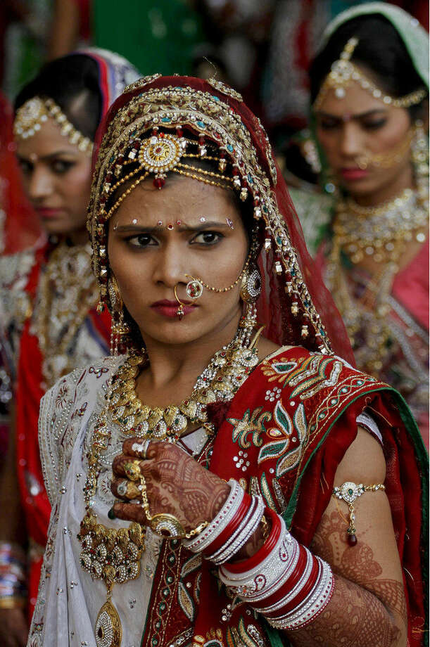 Indian brides wait for transport before a mass wedding hosted by a diamond trader in Surat, India, Sunday, Dec. 6, 2015. 151 young couples tied the knot at the mass wedding hosted by Indian diamond trader Mahesh Savani, who has been funding the weddings of fatherless women in the city of Surat for several years. Weddings in India are expensive affairs with the bride's family traditionally expected to pay the groom a large dowry of cash and gifts. Hundreds of people, mostly family members and neighbors of the couple, are hosted at lavish meals over a number of days adding to the costs. (AP Photo/Ajit Solanki)