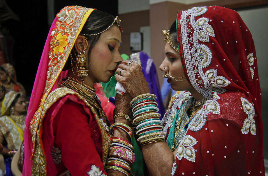 An Indian bride helps another with her attire during a mass wedding hosted by a diamond trader in Surat, India, Sunday, Dec. 6, 2015. 151 young couples tied the knot at the mass wedding hosted by Indian diamond trader Mahesh Savani, who has been funding the weddings of fatherless women in the city of Surat for several years. Weddings in India are expensive affairs with the bride's family traditionally expected to pay the groom a large dowry of cash and gifts. Hundreds of people, mostly family members and neighbors of the couple, are hosted at lavish meals over a number of days adding to the costs. (AP Photo/Ajit Solanki)