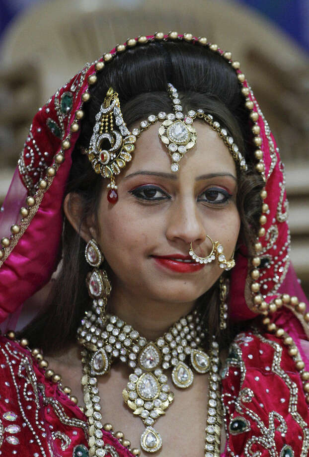 Indian Muslim bride Nagmabegum Qadri looks during a group photo session before a mass wedding hosted by a diamond trader in Surat, India, Sunday, Dec. 6, 2015. 151 young couples tied the knot at the mass wedding hosted by Indian diamond trader Mahesh Savani, who has been funding the weddings of fatherless women in the city of Surat for several years. Weddings in India are expensive affairs with the bride's family traditionally expected to pay the groom a large dowry of cash and gifts. Hundreds of people, mostly family members and neighbors of the couple, are hosted at lavish meals over a number of days adding to the costs. (AP Photo/Ajit Solanki)