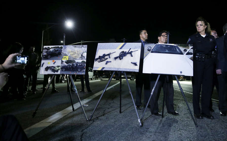 Police crime photos are displayed during a news conference near the site of yesterday's mass shooting on Thursday, Dec. 3, 2015 in San Bernardino, Calif. A husband and wife on Wednesday, dressed for battle and carrying assault rifles and handguns, opened fire on a holiday banquet for his co-workers, killing at least 14 people and seriously wounding more than a dozen others in a precision assault, authorities said. Hours later, the couple died in a shootout with police. (AP Photo/Chris Carlson)