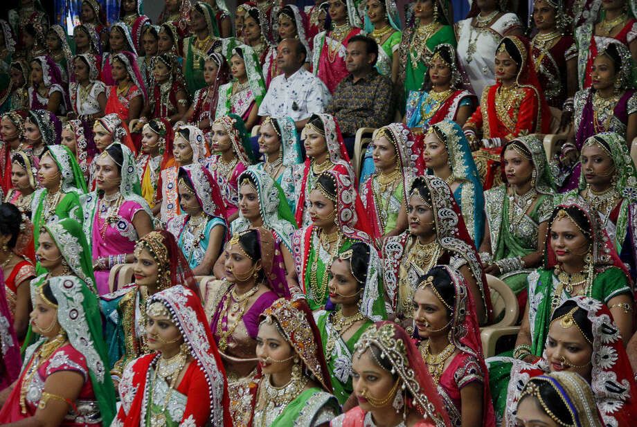 Indian diamond trader Mahesh Savani, top center wearing white, poses for a group photo along with brides before mass wedding hosted by him in Surat, India, Sunday, Dec. 6, 2015. 151 young couples tied the knot at the mass wedding hosted by Savani who has been funding the weddings of fatherless women in the city of Surat for several years. Weddings in India are expensive affairs with the bride's family traditionally expected to pay the groom a large dowry of cash and gifts. Hundreds of people, mostly family members and neighbors of the couple, are hosted at lavish meals over a number of days adding to the costs. (AP Photo/Ajit Solanki)