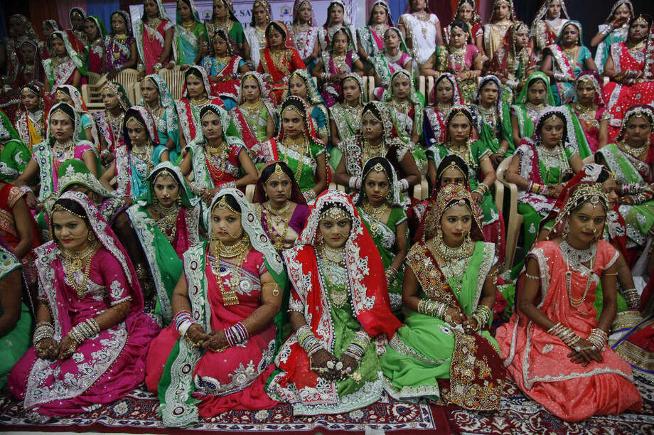 Indian brides sit for a group photo before a mass wedding hosted by a diamond trader in Surat, India, Sunday, Dec. 6, 2015. 151 young couples tied the knot at the mass wedding hosted by Indian diamond trader Mahesh Savani, who has been funding the weddings of fatherless women in the city of Surat for several years. Weddings in India are expensive affairs with the bride's family traditionally expected to pay the groom a large dowry of cash and gifts. Hundreds of people, mostly family members and neighbors of the couple, are hosted at lavish meals over a number of days adding to the costs. (AP Photo/Ajit Solanki)