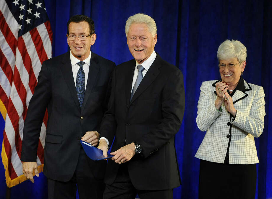 Gov. Dannel P. Malloy, left, greets former President Bill Clinton, center, as Lt. Gov. Nancy Wyman looks on, at a rally, Monday, Oct. 13, 2014, in Hartford, Conn. (AP Photo/Jessica Hill)