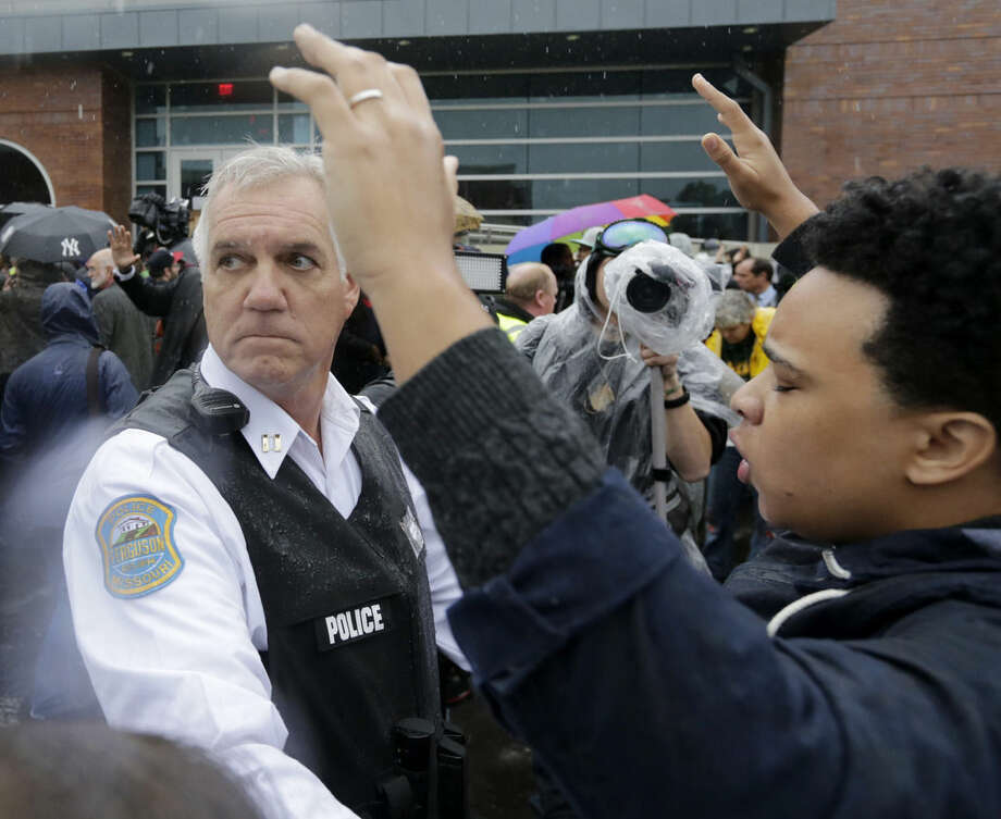 A police officer looks back for help as he tries to keep protesters from advancing farther into the parking lot at the Ferguson, Mo., police station Monday, Oct. 13, 2014. Activists have planed a day of civil disobedience to protest the shooting of Michael Brown and a second police shooting in St. Louis. (AP Photo/Charles Rex Arbogast)