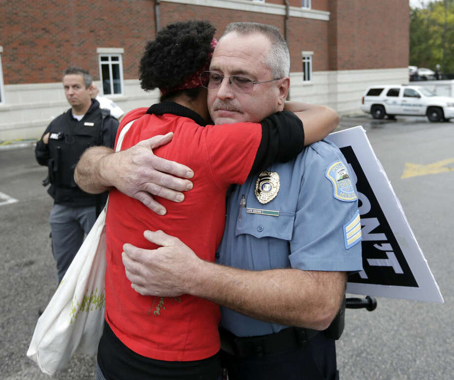 A woman who identified herself as Dragonfly, from the Brooklyn borough of New York, gets a hug from Ferguson, Mo., police Sgt. Michael Wood, after sharing her fear of police brutality with Wood, during a protest at the police station, Monday, Oct. 13, 2014, in Ferguson, Mo. Activists planned a day of civil disobedience to protest the shooting of Michael Brown, in August, and a second police shooting in St. Louis last week. (AP Photo/Charles Rex Arbogast)