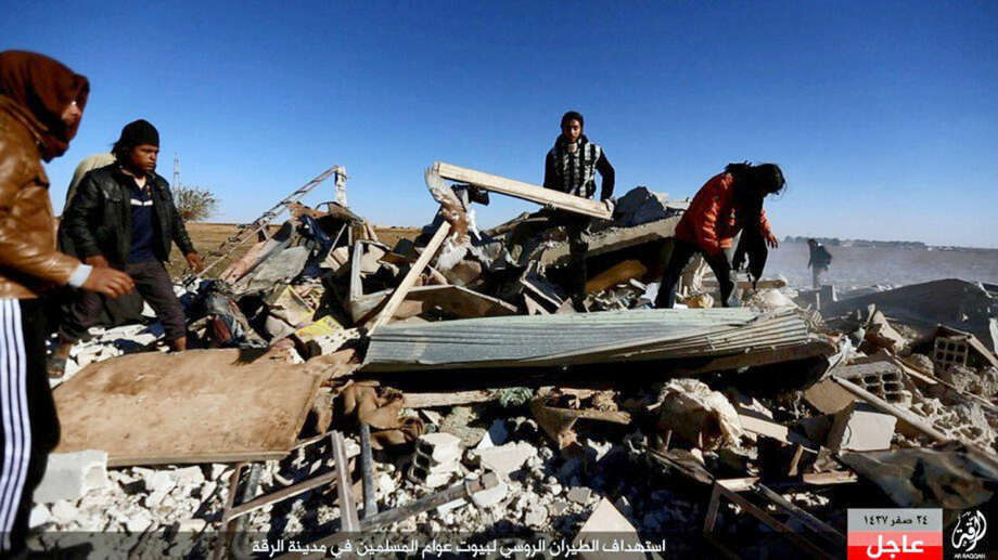 """This image posted online Sunday, Dec. 6, 2015, by supporters of the Islamic State militant group on an anonymous photo sharing website, shows Syrians inspecting a damaged building in the aftermath of an airstrike that targeted areas in Raqqa, Syria. The photo bears the watermark of Islamic State media releases and is consistent with other AP reporting. The Arabic caption on the photo reads, """"Russian warplanes target homes of Muslims in Raqqa."""" (militant photo via AP)"""