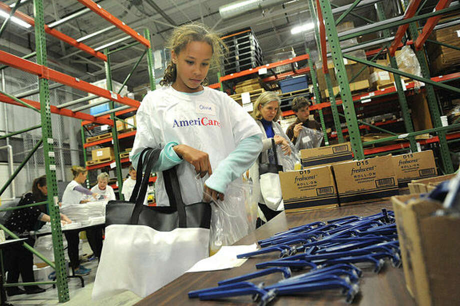Olivia Rwambuya Tuesday helping to assemble family emergency kits at AmeriCares in Stamford.