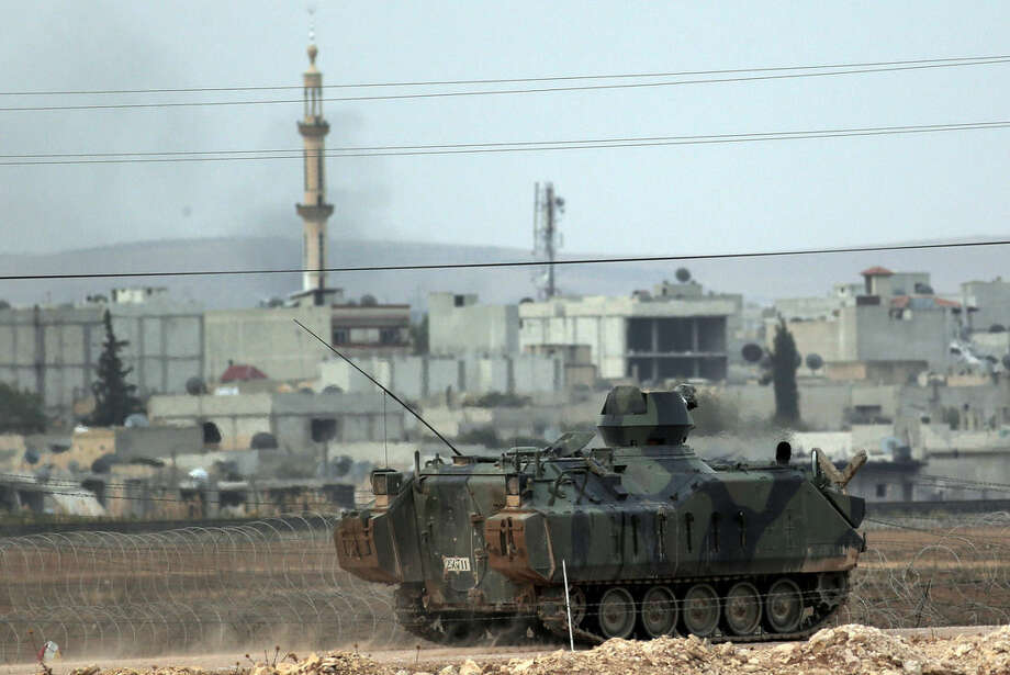 Backdropped by Kobani, in Syria, a Turkish forces armoured vehicle patrols the border road in Mursitpinar, on the outskirts of Suruc, on the Turkey-Syria border, where in Kobani fighting between Syrian Kurds and the militants of Islamic State group continued, Tuesday, Oct. 14, 2014. Kobani, also known as Ayn Arab, and its surrounding areas, has been under assault by extremists of the Islamic State group since mid-September and is being defended by Kurdish fighters. (AP Photo/Lefteris Pitarakis)