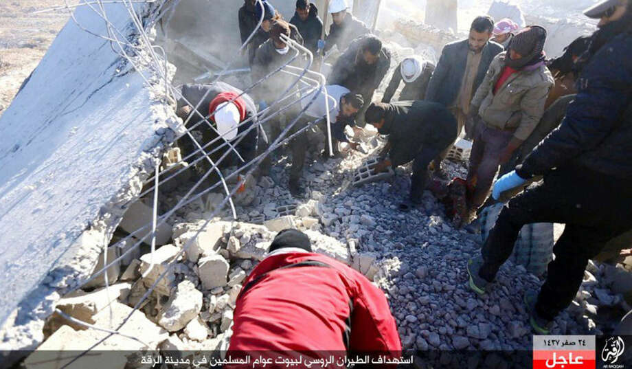 "This image posted online Sunday, Dec. 6, 2015, by supporters of the Islamic State militant group on an anonymous photo sharing website, shows Syrians inspecting a damaged building in the aftermath of an airstrike that targeted areas in Raqqa, Syria. The photo bears the watermark of Islamic State media releases and is consistent with other AP reporting. The Arabic caption on the photo reads, ""Russian warplanes target homes of Muslims in Raqqa."" (militant photo via AP)"