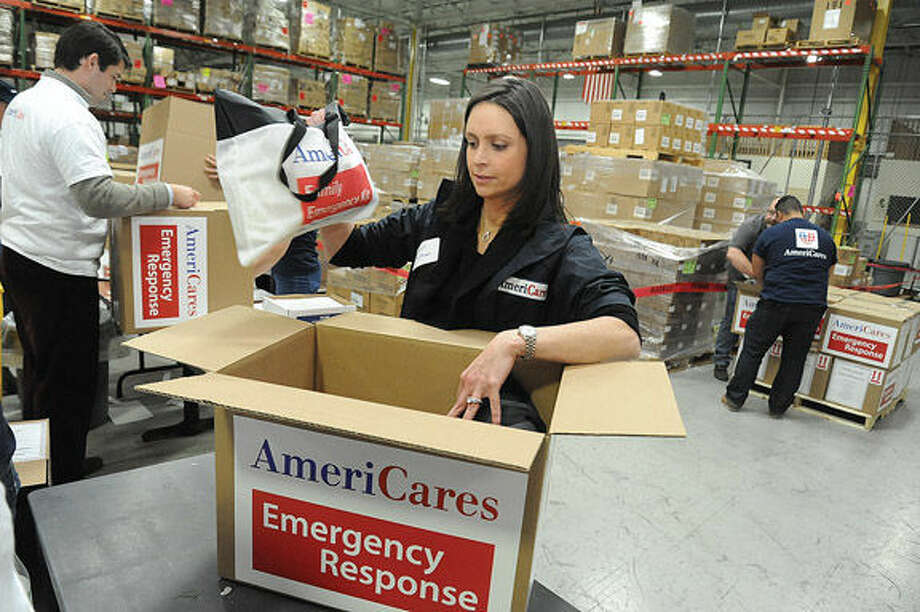 Megin Wolfman, a corporate officer at AmeriCares, helps pack emergency kits at the global relief organization's Stamford headquarters Tuesday evening.