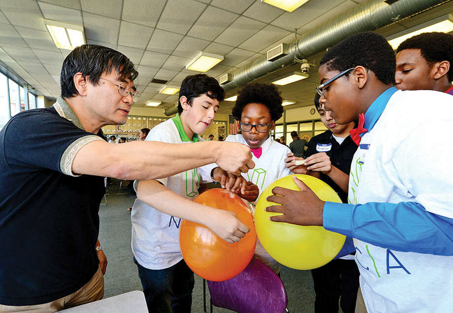 Hour photo / Erik Trautmann IBM employee and mentor Young Kwark helps Norwalk High School mentees Felipe Buitrago, Shamar Askew and Kevin Cayl in a balloon rocket experiment as Norwalk Early College Academy (NECA) and IBM kick-off the school's new mentoring program Friday at Norwalk Communtiy College. NECA is the state's first Pathways in Technology Early College High School (P-TECH). The 9-14 Model School, a collaboration among IBM, Norwalk Public Schools and Norwalk Community College, pairs each student with an IBM mentor, providing students with support and guidance to develop the employability skills needed to succeed in today's workforce. Students who successfully complete the six-year program, which spans grades 9 to 14, graduate with a no-cost Associate in Applied Science degree and will be first in line for available jobs at IBM.