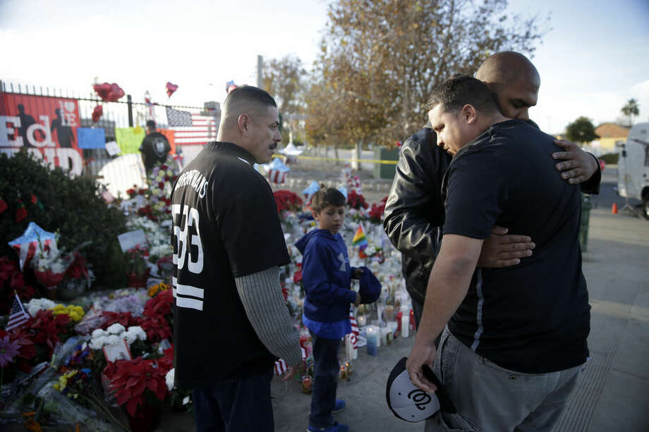 Mourners comfort each other at a makeshift memorial site honoring Wednesday's shooting victims Monday, Dec. 7, 2015 in San Bernardino, Calif. Thousands of employees of San Bernardino County are preparing to return to work Monday, five days after a county restaurant inspector and his wife opened fire on a gathering of his co-workers, killing 14 people and wounding 21. (AP Photo/Jae C. Hong)