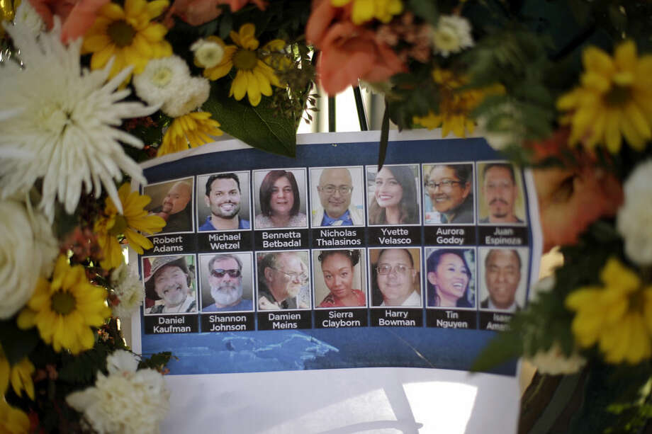 Pictures of Wednesday's shooting victims are displayed at a makeshift memorial site Monday, Dec. 7, 2015 in San Bernardino, Calif. Thousands of employees of San Bernardino County are preparing to return to work Monday, five days after a county restaurant inspector and his wife opened fire on a gathering of his co-workers, killing 14 people and wounding 21. (AP Photo/Jae C. Hong)