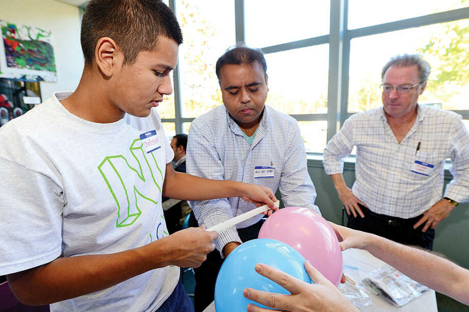 Hour photo / Erik Trautmann Norwalk High School student and mentee Christopher Vega and IBM employees and mentors Parijat Dube and Michael Gordon work together on a balloon rocket experiment as Norwalk Early College Academy (NECA) and IBM kick-off the school's new mentoring program Friday at Norwalk Communtiy College. NECA is the state's first Pathways in Technology Early College High School (P-TECH). The 9-14 Model School, a collaboration among IBM, Norwalk Public Schools and Norwalk Community College, pairs each student with an IBM mentor, providing students with support and guidance to develop the employability skills needed to succeed in today's workforce. Students who successfully complete the six-year program, which spans grades 9 to 14, graduate with a no-cost Associate in Applied Science degree and will be first in line for available jobs at IBM.