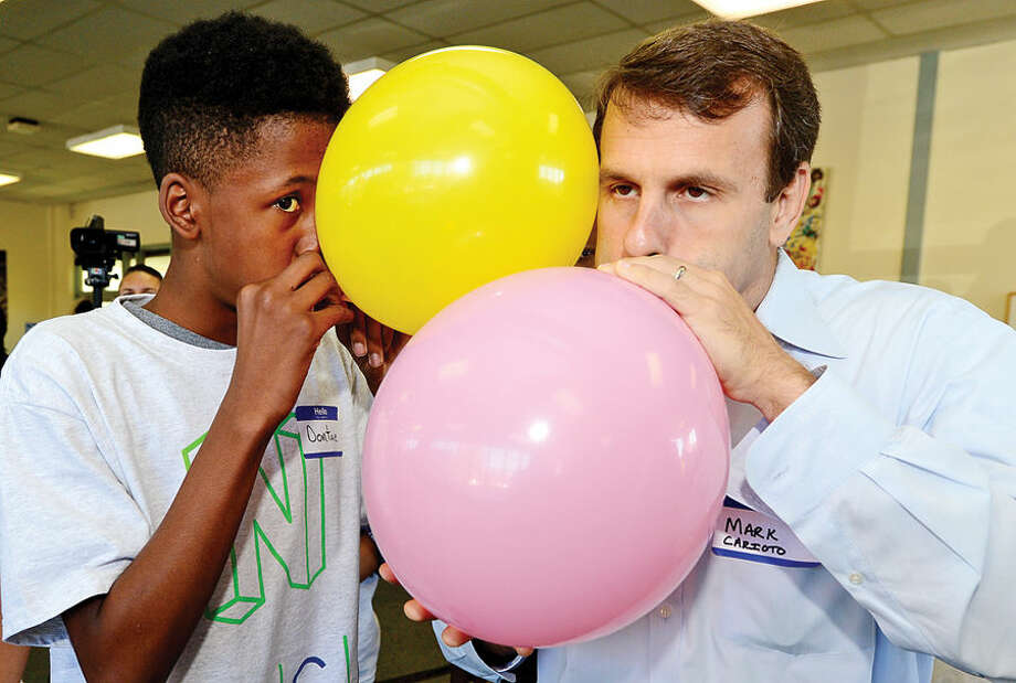 Hour photo / Erik Trautmann Norwalk High School student and mentee Dontae King and IBM employee and mentor Mark Carioto work together on a balloon rocket experiment as Norwalk Early College Academy (NECA) and IBM kick-off the school's new mentoring program Friday at Norwalk Communtiy College. NECA is the state's first Pathways in Technology Early College High School (P-TECH). The 9-14 Model School, a collaboration among IBM, Norwalk Public Schools and Norwalk Community College, pairs each student with an IBM mentor, providing students with support and guidance to develop the employability skills needed to succeed in today's workforce. Students who successfully complete the six-year program, which spans grades 9 to 14, graduate with a no-cost Associate in Applied Science degree and will be first in line for available jobs at IBM.