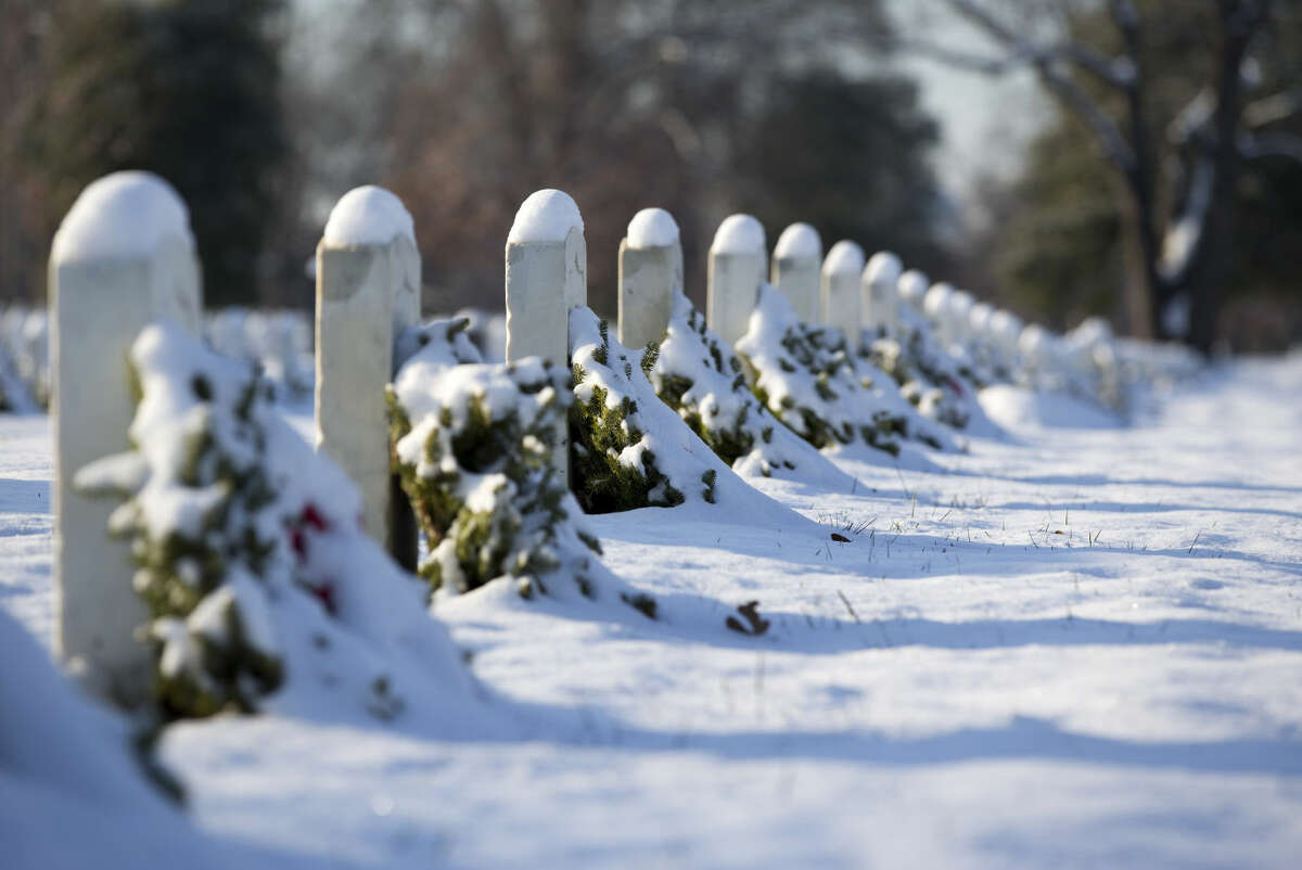 In this file photo, snow covers wreaths and tombstones at Arlington National Cemetery in Arlington, Va., Tuesday, Jan. 6, 2015, after a snow storm hit the Washington area. (AP Photo/Manuel Balce Ceneta)