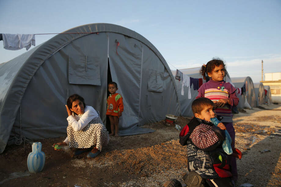 Syrian Kurdish refugees who fled fighting in Kobani, Syria, go about at a refugee camp in Suruc, on the Turkey-Syria border, Friday, Oct. 17, 2014. Kobani, also known as Ayn Arab, and its surrounding areas, has been under assault by extremists of the Islamic State group since mid-September and is being defended by Kurdish fighters. The onslaught has forced more than 200,000 people to flee across the border into Turkey. (AP Photo/Lefteris Pitarakis)