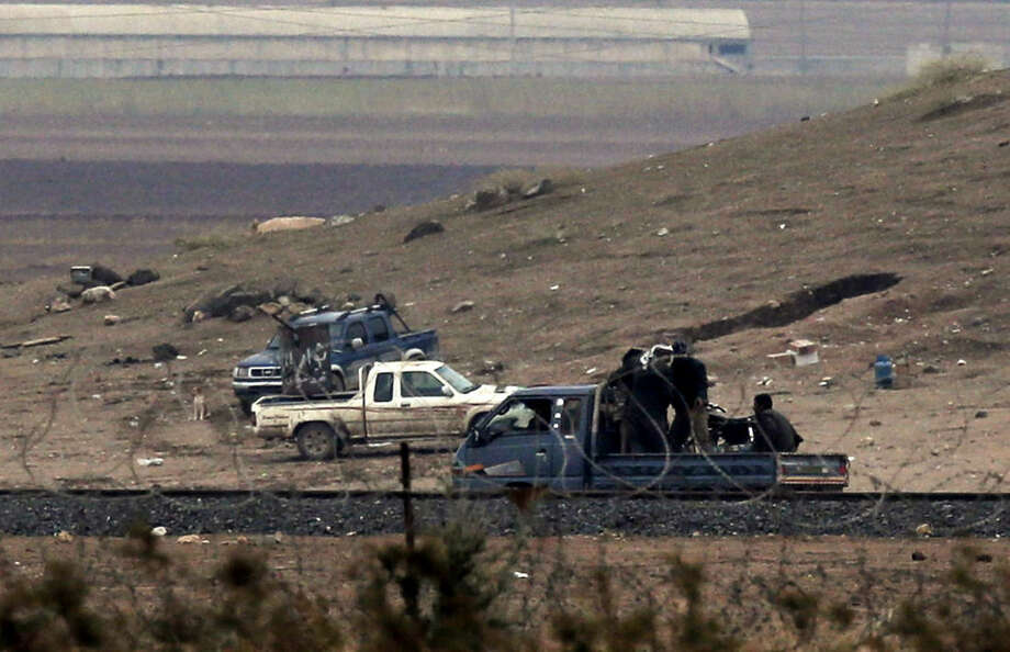 In this image shot with an extreme telephoto lens from the outskirts of Suruc at the Turkey-Syria border, Kurdish fighters with The People's Protection Units, or YPG, the main Kurdish militia in Syria, drive past a machine gun-fitted pick-up truck belonging to the group as they patrol the border road on the outskirts of western Kobani, Syria, during fighting between Syrian Kurds and the militants of Islamic State group, Friday, Oct. 17, 2014. Kobani, also known as Ayn Arab, and its surrounding areas, has been under assault by extremists of the Islamic State group since mid-September and is being defended by Kurdish fighters. (AP Photo/Lefteris Pitarakis)