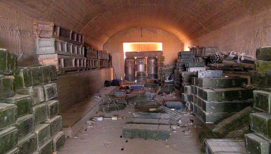 This undated image posted Aug. 27, 2014 by the Raqqa Media Center of the Islamic State group, a Syrian opposition group, which has been verified and is consistent with other AP reporting, shows a munitions warehouse that was captured by the Islamic State group in the battle for the Tabqa air base in Raqqa, Syria. The Islamic State group is test flying, with the help of former Iraqi air force pilots, several fighter jets captured earlier from air bases belonging to the Syrian military, a Syrian activist group said Friday, Oct. 17, 2014. The report by the Britain-based Syrian Observatory for Human Rights could not be independently confirmed, and U.S. official said they had no reports of Islamic State group militants flying jets in support of their forces on the ground.(AP Photo/ Raqqa Media Center of the Islamic State group)