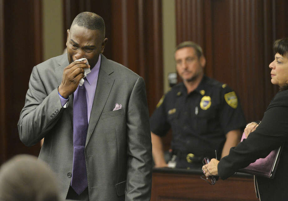 Ron Davis, the father of Jordan Davis, wipes away tears after reading his victim's impact statement to the court, during Michael Dunn's sentencing hearing, Friday, Oct. 17, 2014, at the Duval County Courthouse in Jacksonville, Fla. Dunn, convicted of first-degree murder in a retrial in September for fatally shooting 17-year-old Jordan Davis in November 2012 in an argument over loud music outside a Florida convenience store, was sentenced to life in prison without parole. (AP Photo/The Florida Times-Union, Bruce Lipsky, Pool)