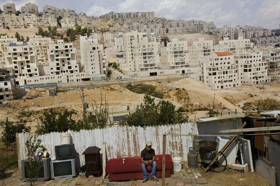 """FILE -- In this Monday, Sept. 21, 2009 file photo, a Palestinian boy sits in the yard of his house, back-dropped by the Israeli housing development, Har Homa, in east Jerusalem. An investigation published by the liberal daily Haaretz newspaper Monday, Dec. 7, 2015, said U.S. donors have pumped more than $200 million into Jewish West Bank settlements in recent years. The report says the tax-deductible status of the money means the U.S. was """"incentivizing"""" settlements, which Washington opposes and views as an obstacle to peace. (AP Photo/Bernat Armangue, File)"""