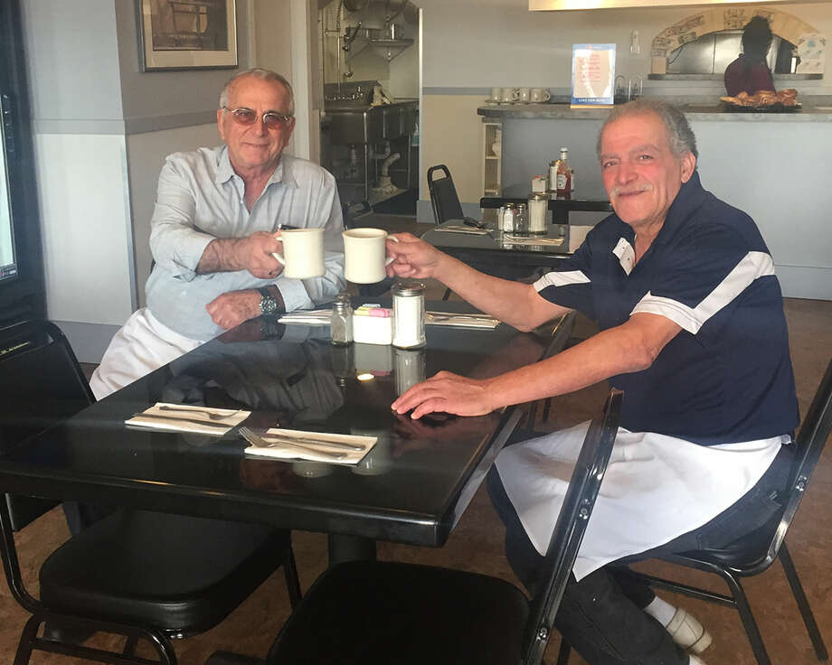 Contributed photoOwners of Oceanview John Kaipides and Magdi Elawadi toast in the new restaurant in Liberty Square in East Norwalk recently.