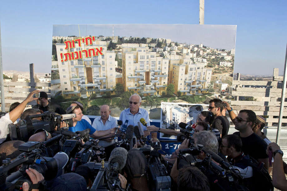 "FILE -- In this Aug. 11, 2013 file photo, Israeli Minister of Housing and Construction Uri Ariel, center, speaks during a ceremony to mark the resumption of the construction of housing units in an east Jerusalem neighborhood. An investigation published by the liberal daily Haaretz newspaper Monday, Dec. 7, 2015, said U.S. donors have pumped more than $200 million into Jewish West Bank settlements in recent years. The report says the tax-deductible status of the money means the U.S. was ""incentivizing"" settlements, which Washington opposes and views as an obstacle to peace. (AP Photo/Sebastian Scheiner, File)"
