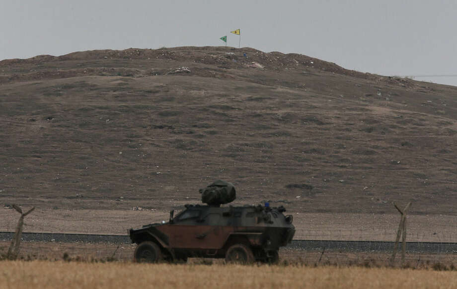 In this image shot with an extreme telephoto lens from the outskirts of Suruc on the Turkey-Syria border, a Turkish armoured vehicle patrols the border road, as flags of The People's Protection Units, or YPG, the main Kurdish militia in Syria, are placed by its fighters on a hilltop on the outskirts of western Kobani, Syria, during fighting between Syrian Kurds and the militants of Islamic State group, Friday, Oct. 17, 2014. Kobani, also known as Ayn Arab, and its surrounding areas, has been under assault by extremists of the Islamic State group since mid-September and is being defended by Kurdish fighters. (AP Photo/Lefteris Pitarakis)