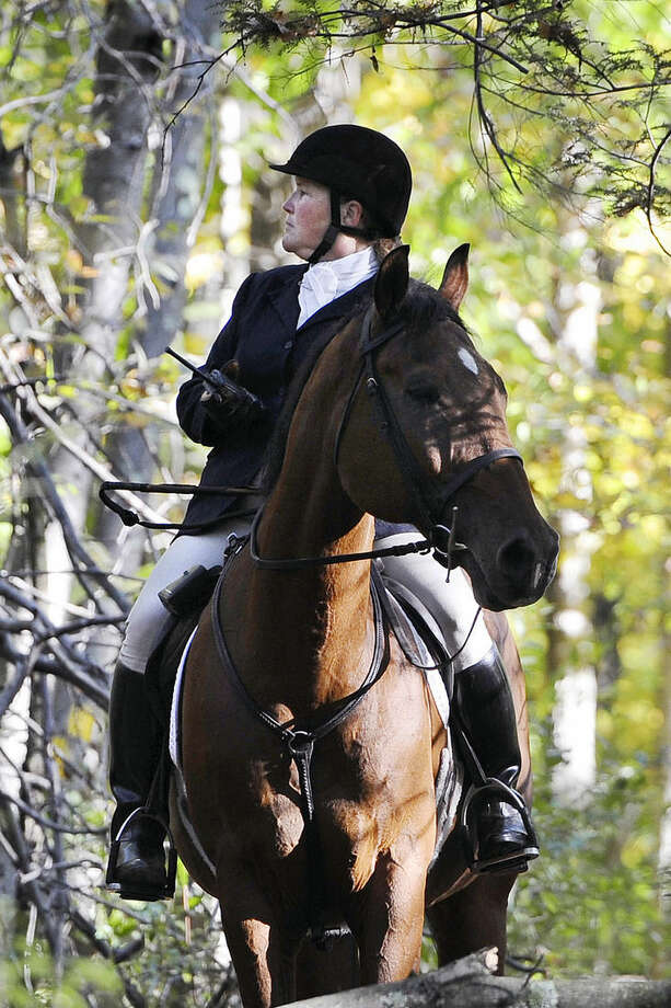 In this Wednesday, Oct. 8, 2014 photo, Cathy Languerand, in the role of whippers-in, looks for a stray hound during a hunt in Bridgewater, Conn. The whippers-in assists the hunters to keep hounds away from the road and within the boundaries of the hunting land. (AP Photo/Jessica Hill)